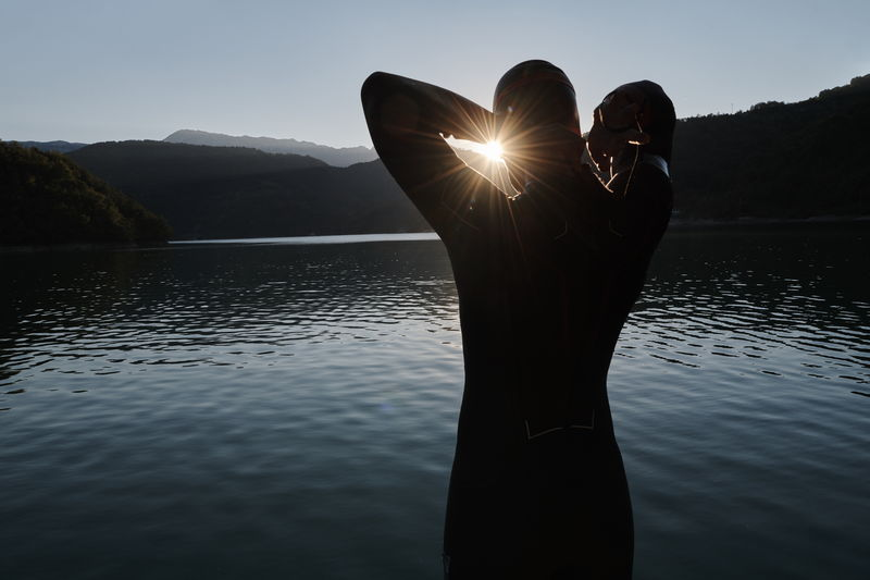 Silhouette person by lake against sky during sunset