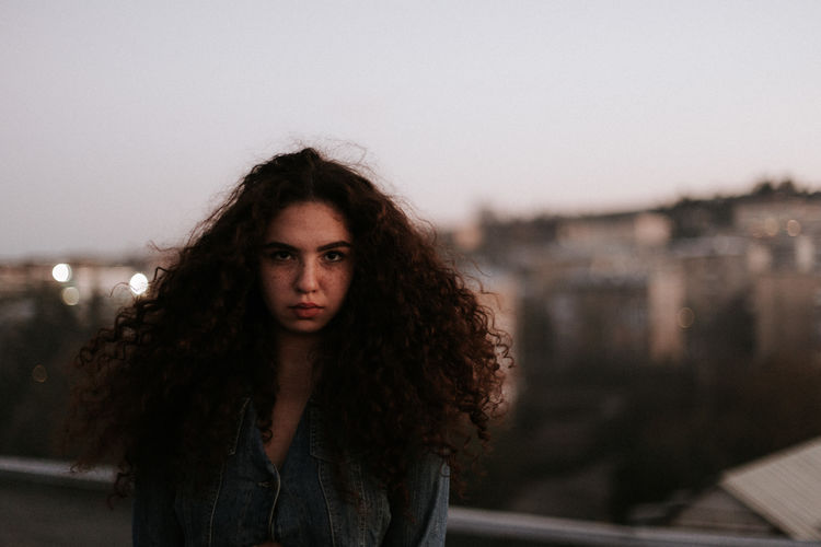 Portrait One Person Looking At Camera Young Adult Hairstyle Hair Long Hair Real People Lifestyles Young Women Sky Focus On Foreground Leisure Activity Architecture Beauty Curly Hair Standing Brown Hair Beautiful Woman Outdoors Contemplation