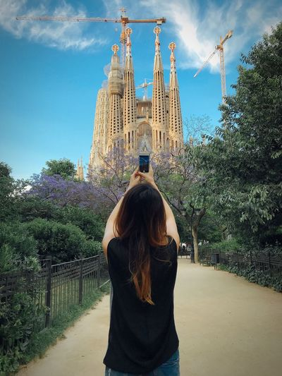 Rear view of woman photographing cathedral through smart phone against sky