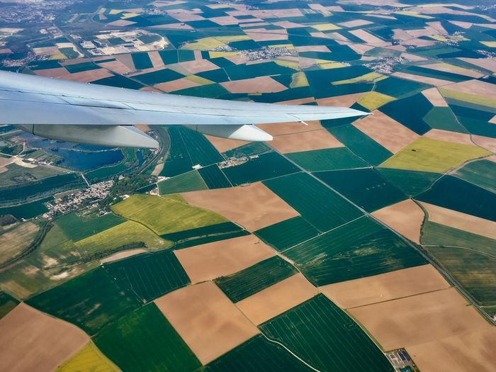 Cropped image of aircraft wing over patchwork landscape