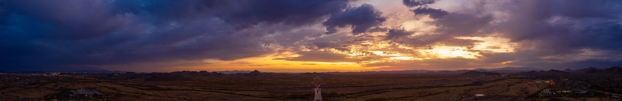 Panoramic view of landscape against dramatic sky during sunset