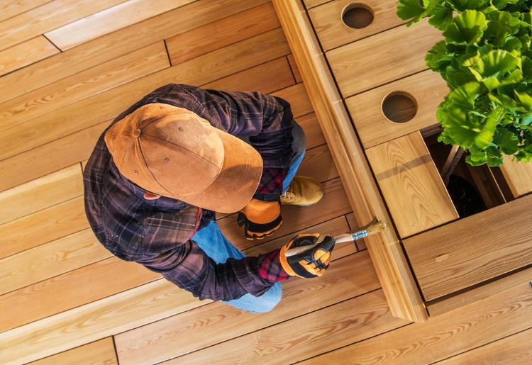 High angle view of man varnishing furniture at home