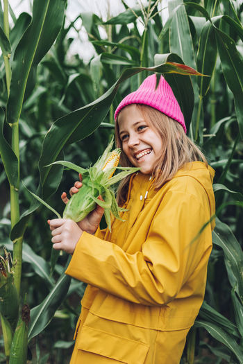 Woman holding yellow while standing by plants