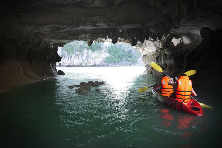 Rear view of people kayaking in cave