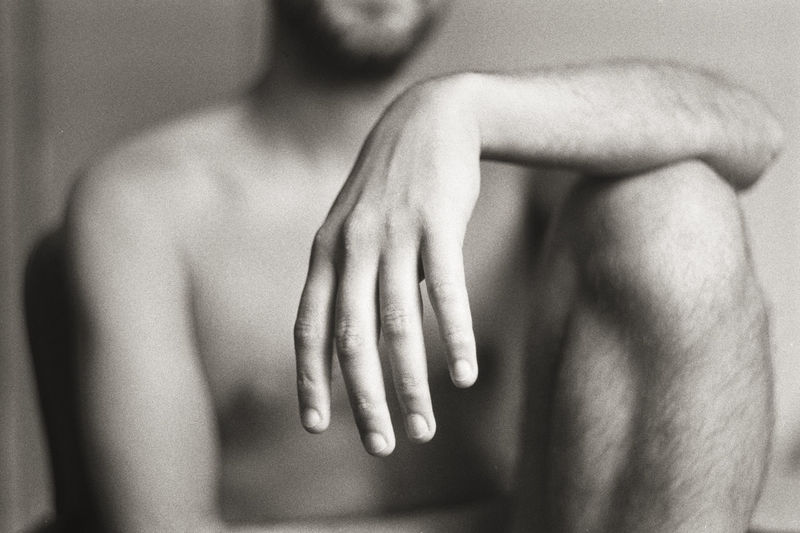 Midsection of naked man sitting against wall at home