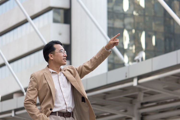 Well-dressed businessman pointing while standing against modern buildings in city