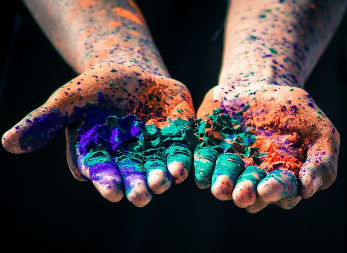 Cropped image of hands with multi colored powder paints over black background