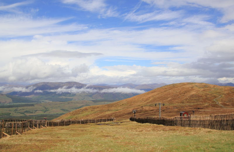 Scenic view of landscape and aonach mor mountains against cloudy sky