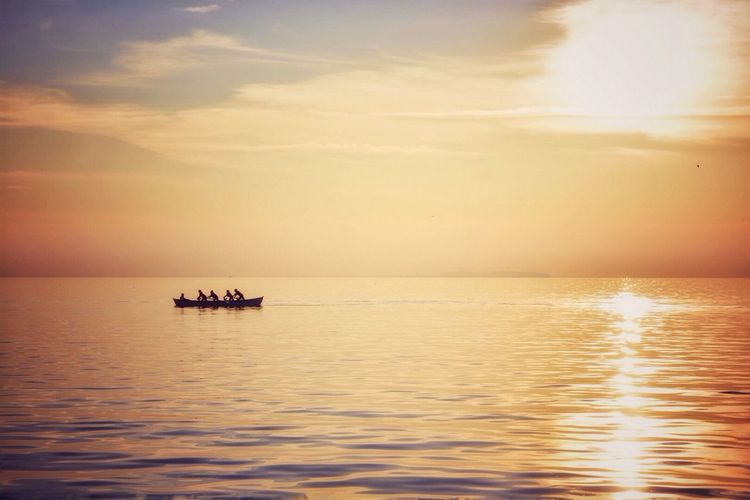 Scenic view of sea against sky during sunset with silhouette of canoe