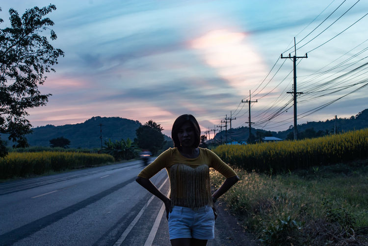 Portrait of woman standing on roadside against sky during sunset