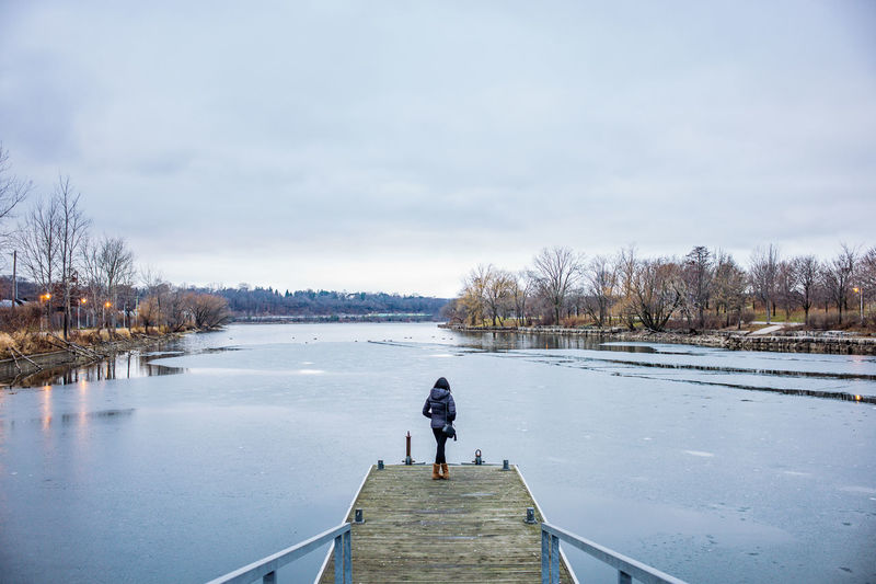 Rear view of woman on ice covered lake against sky