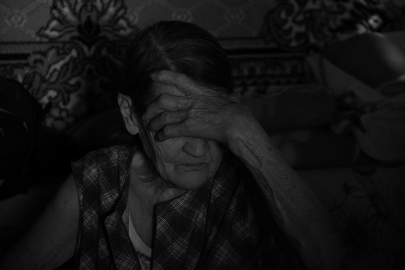 Senior Woman Sitting With Head In Hands At Home