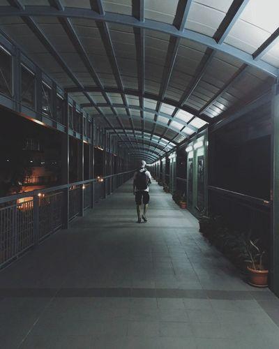 Full Length Of Man Walking On Elevated Walkway At Night