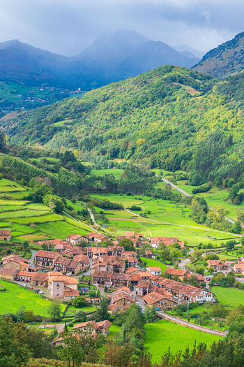 High angle view of houses on field against mountain