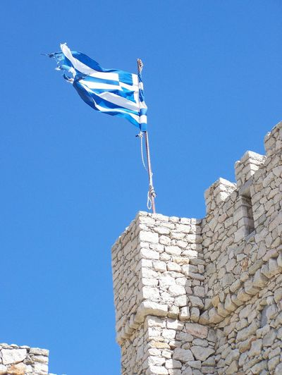 Low angle view of greek flag waving on fort against clear blue sky
