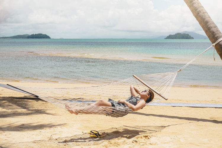 Woman lying on hammock at beach against sky