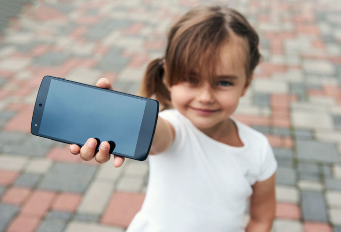 Adorable little girl with a smartphone outdoors. 5 Years Old Alone Beautiful Caucasian Cell Cellphone Child Concept Daughter Device Gaming Hand Holding Internet Little Girl Mobile Phone Outdoors Phone Player Positive Selective Focus Small Girl Smartphone Summer Technology