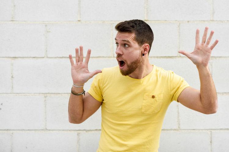 Shocked man gesturing against wall