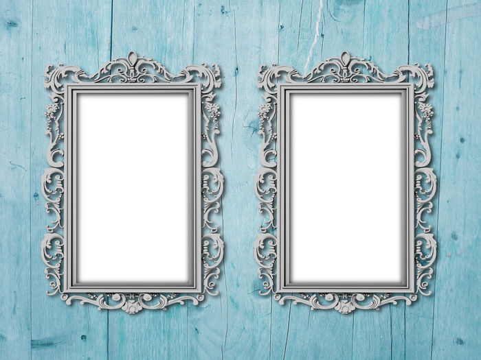 Blank frames on green wooden wall