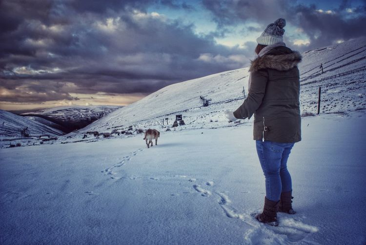 Woman Standing On Snowy Field Against Cloudy Sky During Sunset