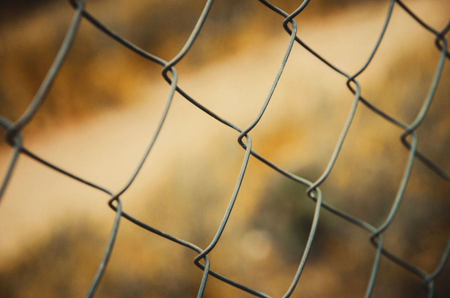 Mesh fence close-up, country road in background Backgrounds Barrier Boundary Chainlink Fence Close-up Day Fence Focus On Foreground Full Frame Mesh Fence Metal Nature No People Outdoors Pattern Protection Safety Security Sport Wire Wire Mesh