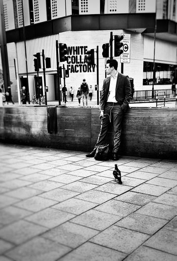 Man with umbrella on sidewalk in city