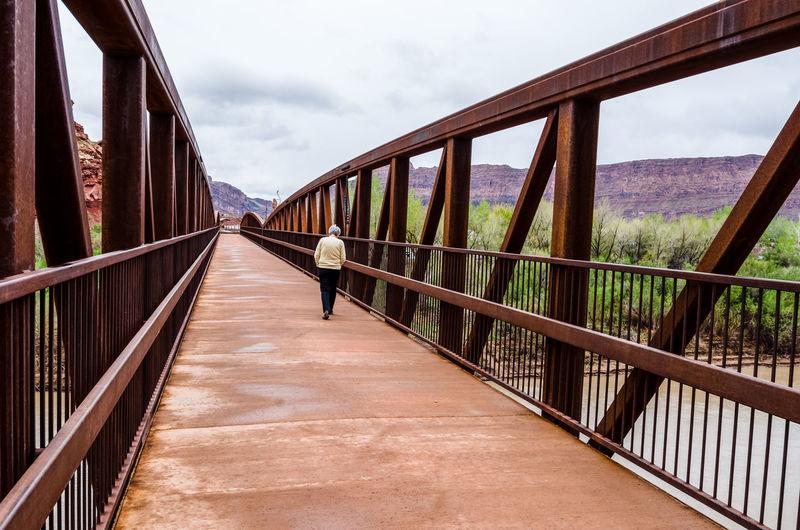Footbridge Leading Towards Bridge Against Sky