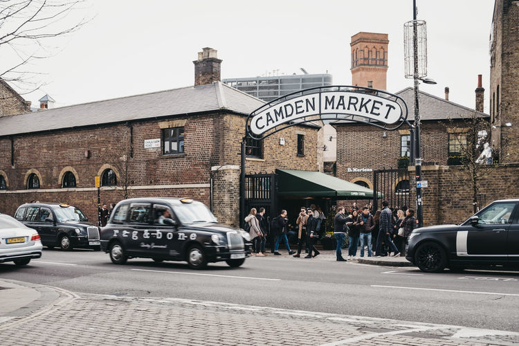 Taxis and people in front of Camden Market. Started with 16 stalls in March 1974, Camden Market is one of the busiest retail destinations in London. Crowd Building Real People Incidental People Men Text Sky Day Group Of People Road Land Vehicle Mode Of Transportation Car Transportation Street Motor Vehicle Building Exterior Built Structure City Architecture Tourists People Leisure Activity Travel Destinations Europe England Market Famous Place Weekend Activities Trabel Camden Market, London Camden Town Uk London
