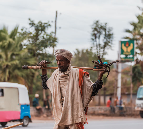 Man holding umbrella standing on road