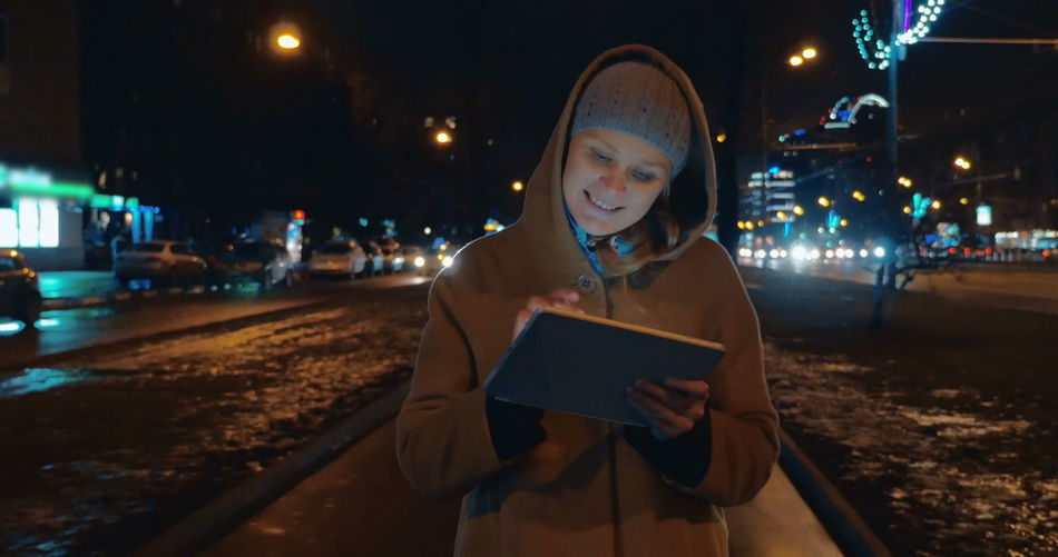 Young woman looking at camera while standing on street in city at night