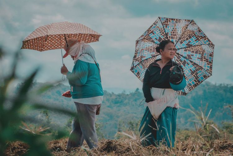 Woman with umbrella standing on land during rainy season