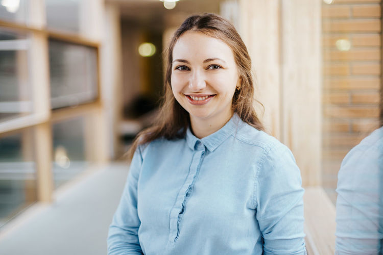 smiling caucasian businesswoman wearing a blue blouse Smiling Portrait Looking At Camera Women Young Adult Happiness Young Women Confidence  Adult Focus On Foreground Indoors  Hairstyle Hair Front View Headshot Beauty One Person Long Hair Beautiful Woman Cheerful Joy Smile Confidence  Confident  Businesswoman