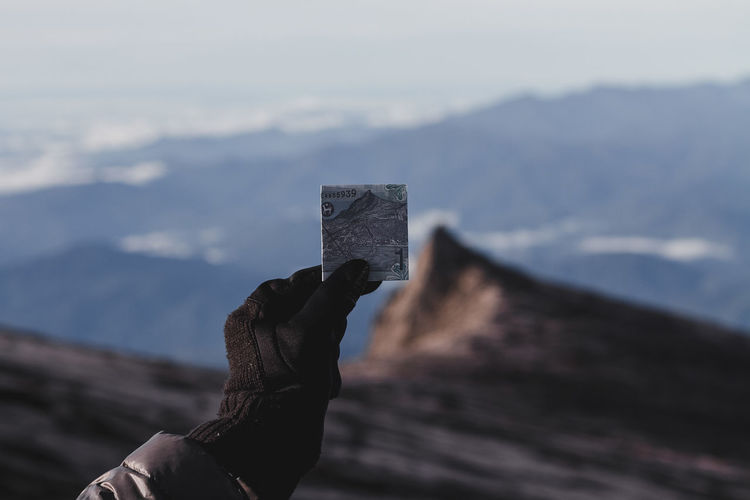 Cropped hand of person holding paper currency on mountains against sky