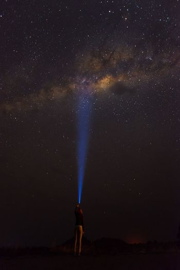 Full length of woman standing against star field at night