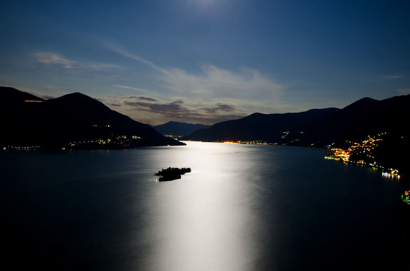 Moonlight over Brissago Islands on alpine lake Maggiore with mountain in Ticino, Switzerland. Alpine Lake Astronomy Beauty In Nature Blue Sky Brissago Islands Cloud Elevated View Idyllic Island Lake Maggiore Landscape Moonlight Mountain Mountain Range Nature Night No People Outdoors Panoramic View Reflection Scenics Silhouette Swiss Alps Tranquil Scene Tranquility