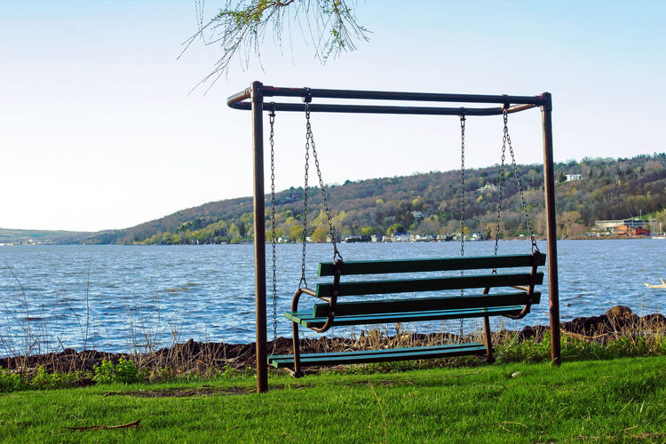 Empty swinging bench by lake against sky