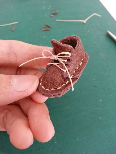 Cropped hand holding tiny leather shoe