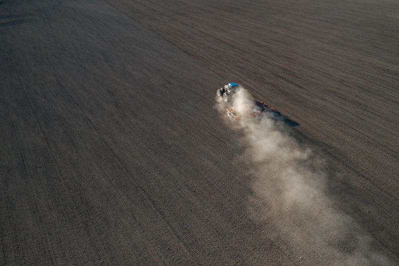 Aerial view of a tractor sowing wheat on agricultural field
