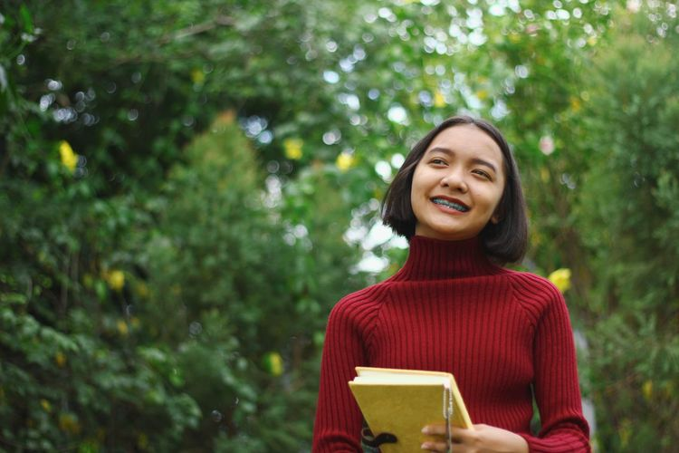 Smiling girl looking away while standing against tree