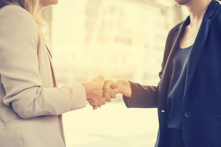 Midsection Of Businesswoman Shaking Hand With Colleague