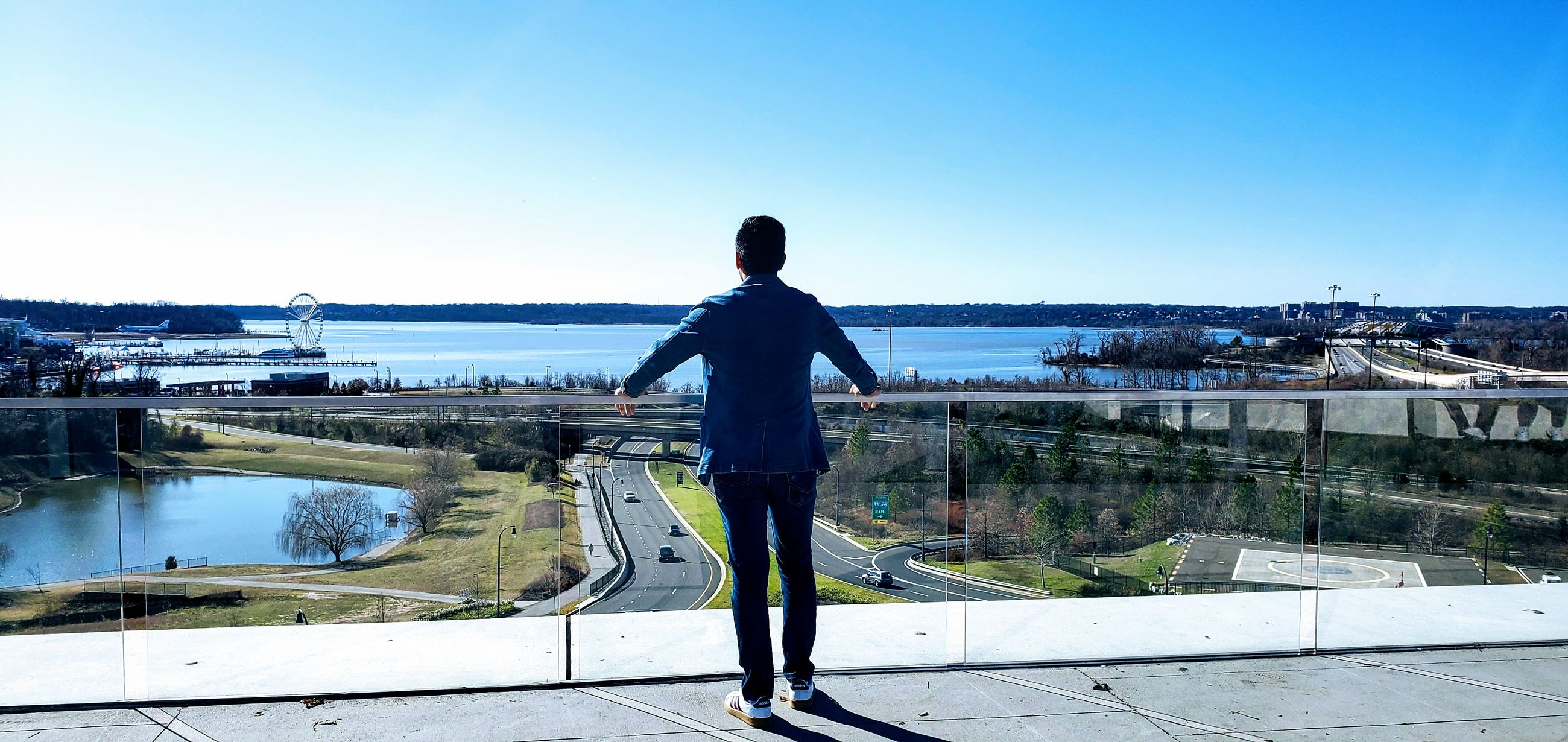 one person, sky, real people, standing, water, rear view, full length, men, nature, lifestyles, casual clothing, day, leisure activity, blue, architecture, clear sky, copy space, scenics - nature, outdoors, looking at view, cityscape