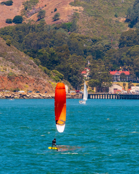 Water Sea Nature Sport Day Adventure Nautical Vessel Waterfront Transportation One Person Leisure Activity Beauty In Nature Real People Tree Mountain Lifestyles Men Plant Aquatic Sport Outdoors Windsurfing