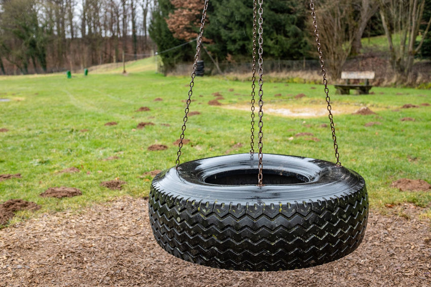 Tree Plant Grass Nature Land Environment Day Metal Outdoors Field No People Playground Tree Trunk Trunk Swing Focus On Foreground Green Color Close-up Rainy Day Boring Car Tyre Chain