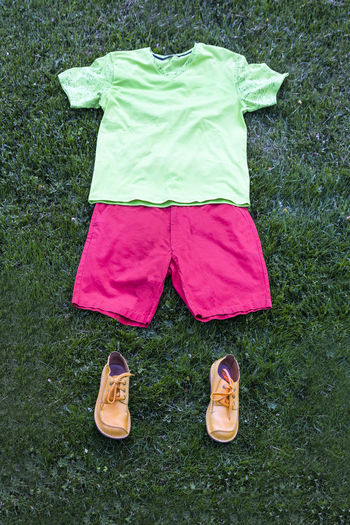 Men`s summer casual clothes and shoes lying in grass. Figure. Casual Casual Clothing Clothes Clothing Directly Above Figure Grass Green Color High Angle View Low Section Nobody Outdoors Pants Shirt Shoes Shorts T-shirt Trousers