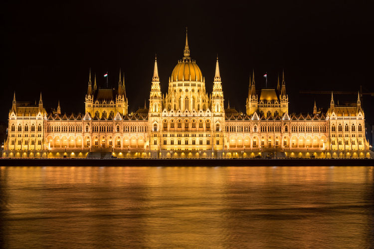 Illuminated Hungarian Parliament Building By Danube River At Night