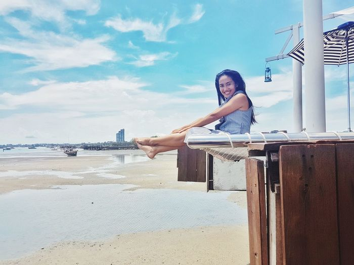 Portrait of smiling woman sitting on built structure at beach against sky