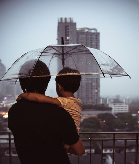 Man and woman with umbrella against building in city