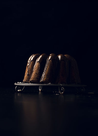 Close-up of cake on table against black background