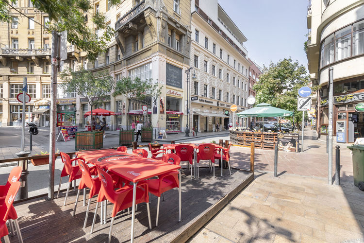 Chairs and tables at sidewalk cafe by buildings in city