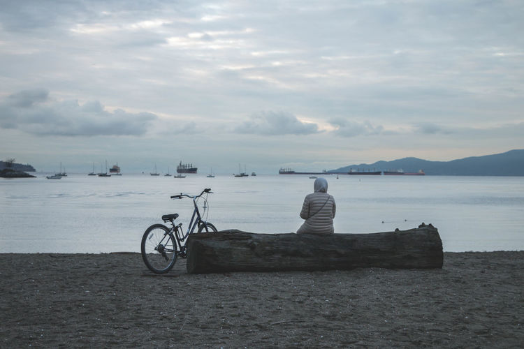 Man on bicycle by sea against sky